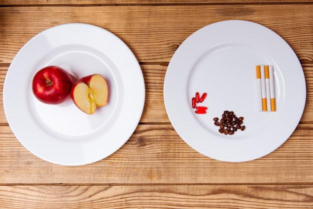 Assiette blanche avec des pilules et des cigarettes sur une table en bois.
