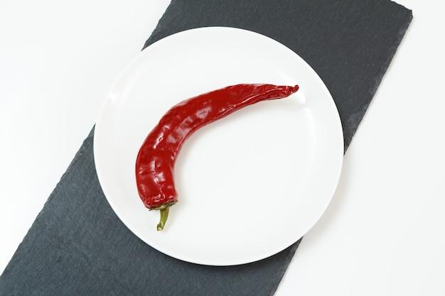 Assiette blanche avec piment frais sur la planche à découper en pierre