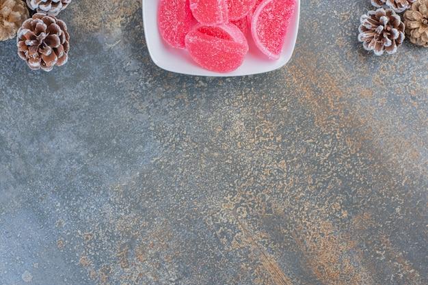 Une assiette blanche pleine de bonbons à la gelée de fruits rouges et de pommes de pin. photo de haute qualité