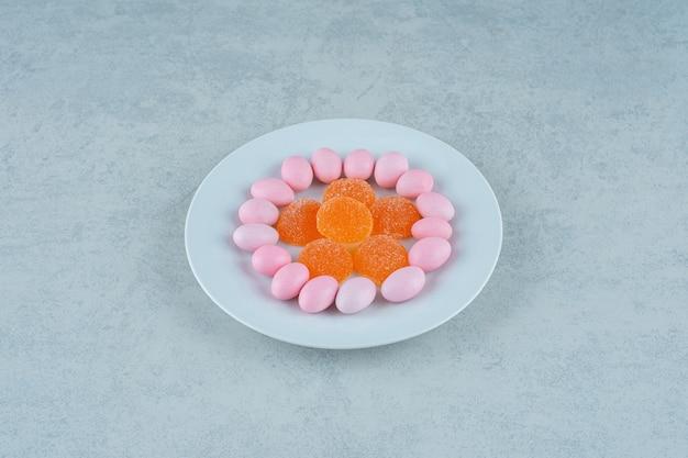 Une assiette blanche pleine de bonbons à la gelée d'orange douce et de bonbons roses
