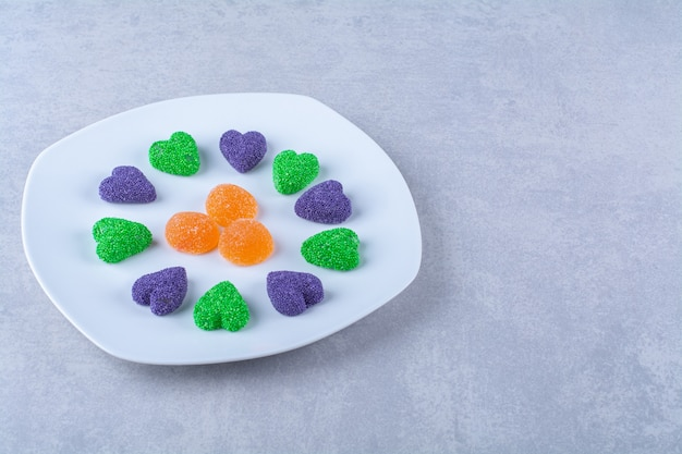 Une assiette blanche pleine de bonbons à la gelée sucrée sur une table grise .
