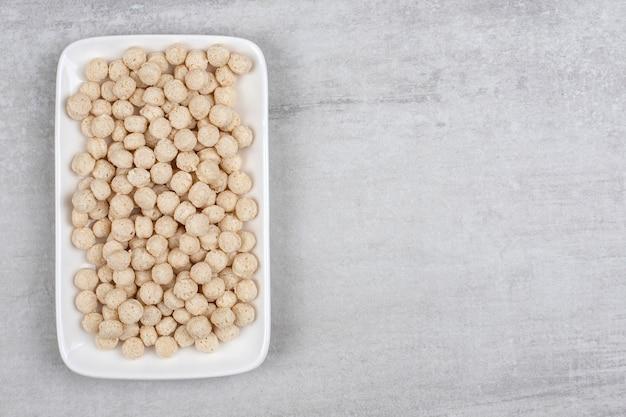 Assiette blanche pleine de boules de céréales de maïs sur pierre.