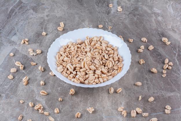 Une assiette blanche pleine de céréales de petit-déjeuner au riz croustillant.