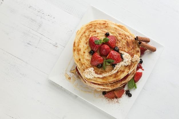 Assiette blanche pleine de crêpes aux fraises framboises myrtilles et miel