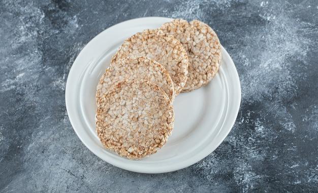 Une assiette blanche pleine de pain de riz soufflé sur une surface en marbre.