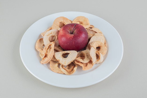 Une assiette blanche pleine de pommes séchées avec une pomme entière.