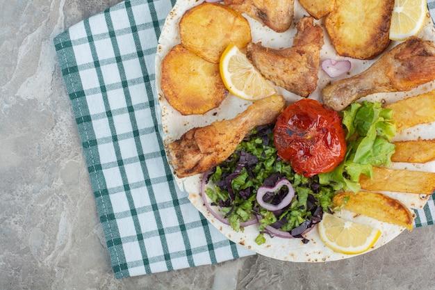 Une assiette blanche pleine de poulet frit et de pommes de terre avec du pain brun.