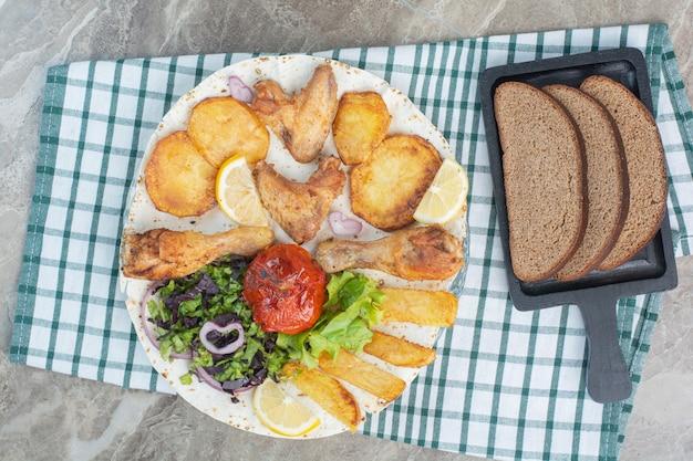 Une assiette blanche pleine de poulet frit et de pommes de terre avec du pain brun