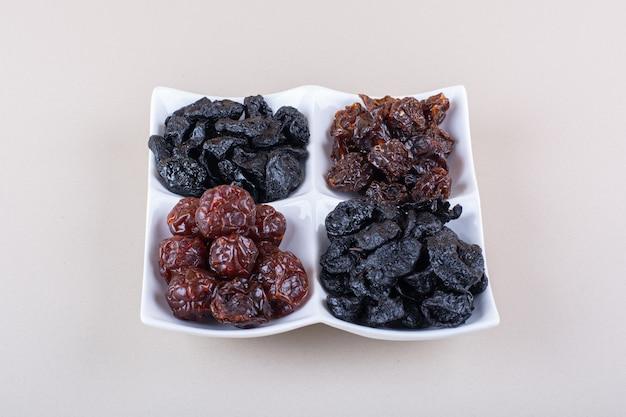 Assiette blanche pleine de prunes savoureuses séchées sur une surface blanche. photo de haute qualité