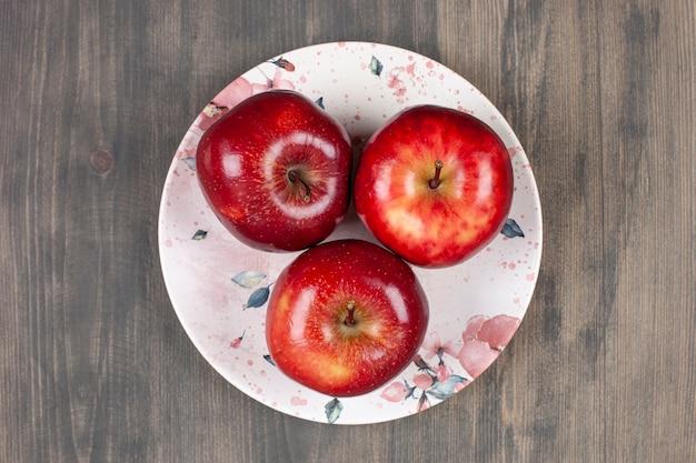 Une assiette blanche avec des pommes juteuses rouges sur une table en bois. photo de haute qualité