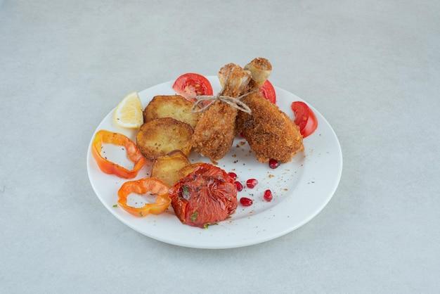Une assiette blanche de poulet frit et de pommes de terre avec des tranches de poivre.