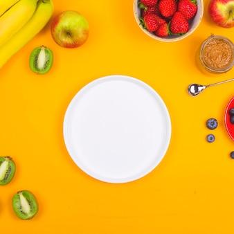 Assiette blanche pour un petit déjeuner sain sur un tableau jaune parmi les fruits.