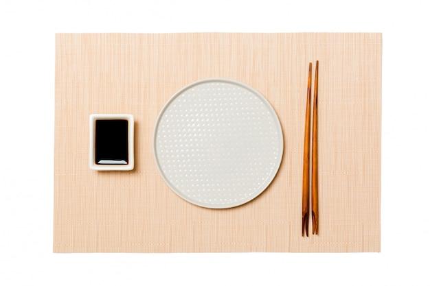 Assiette blanche ronde vide avec des baguettes pour sushi et sauce soja