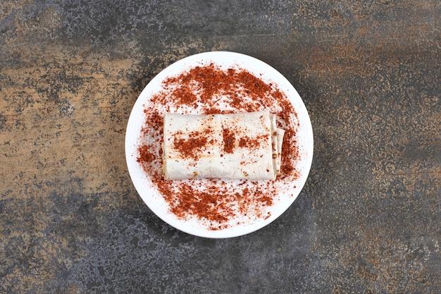 Assiette blanche avec rouleau de viande grillée sur marbre.