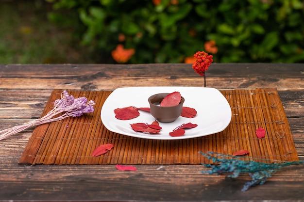 Une assiette blanche située sur le tapis sur laquelle se trouve une tasse en argile avec du lait et un brin de lavande et de pétales d'arbres rouges