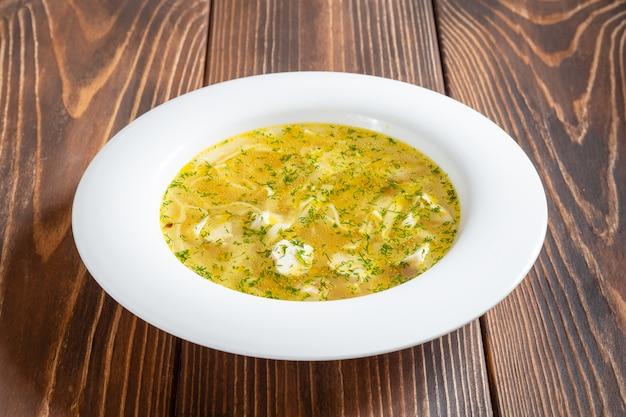 Assiette blanche de soupe au poulet chaud avec des nouilles sur table en bois