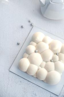 Sur une assiette blanche, une théière et un gâteau mousse fourré à la fraise avec un revêtement blanc velours en forme de bulles
