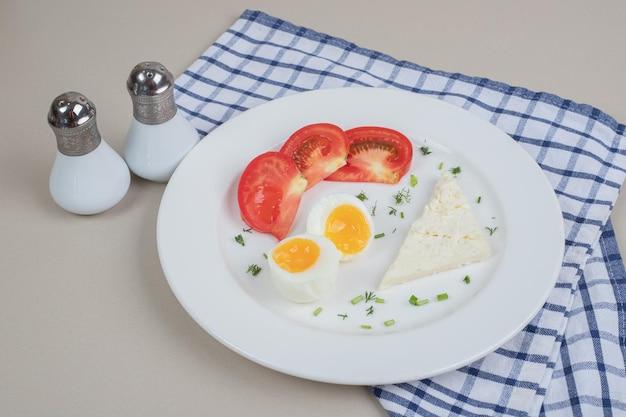 Une assiette blanche de tomates en tranches et œuf à la coque.
