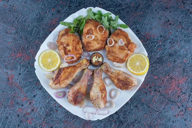 Une assiette blanche avec de la viande de poulet grillée et des tranches de citron.