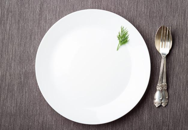 Assiette blanche vide et couverts sur serviette grise