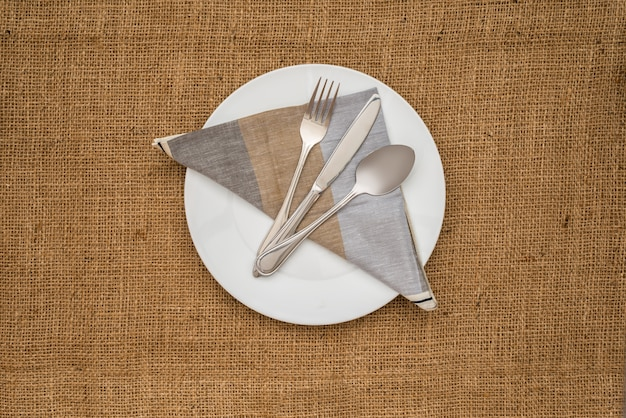 Assiette blanche vide et cuillère, fourchette, couteau, serviette
