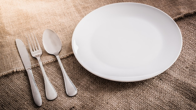 Assiette blanche vide et cuillère, fourchette, couteau