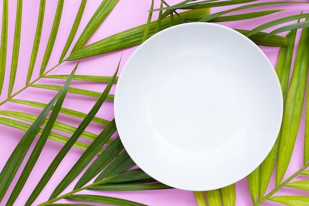 Assiette blanche vide sur des feuilles de palmiers tropicaux sur fond rose.