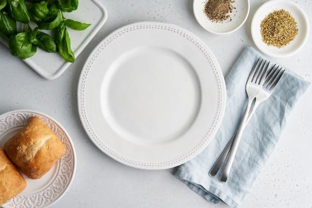 Assiette blanche vide pain laitue épices vaisselle sur fond clair vue de dessus horizontale