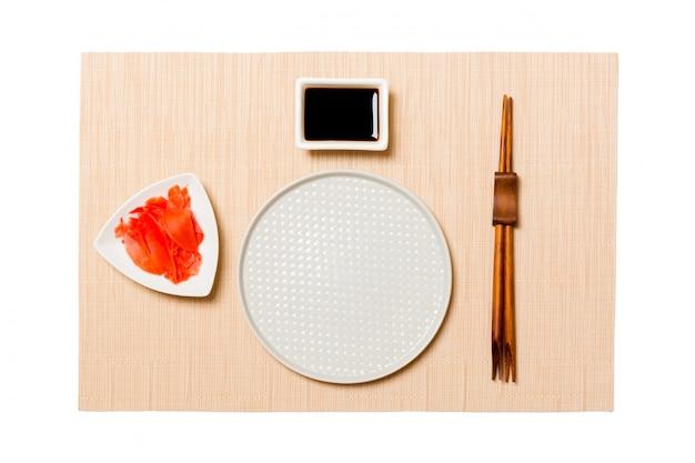 Assiette blanche vide et ronde avec des baguettes pour sushi, gingembre et sauce soja sur tapis de sushi brun. vue de dessus avec espace de copie
