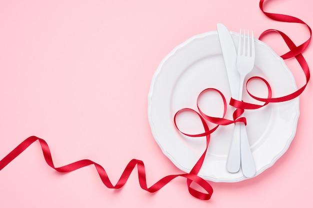 Assiette blanche vide avec ruban rouge. vue de dessus avec espace de copie.