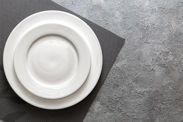 Assiette blanche vide servi sur une serviette en relief et fond de béton gris en relief. vue de dessus maquette pour le menu