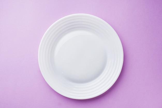 Assiette blanche vide sur une surface rose