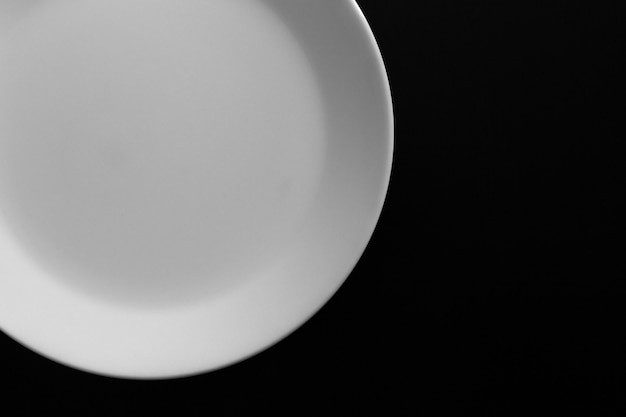 Assiette blanche vide sur table en bois noir. ustensiles de cuisine se bouchent