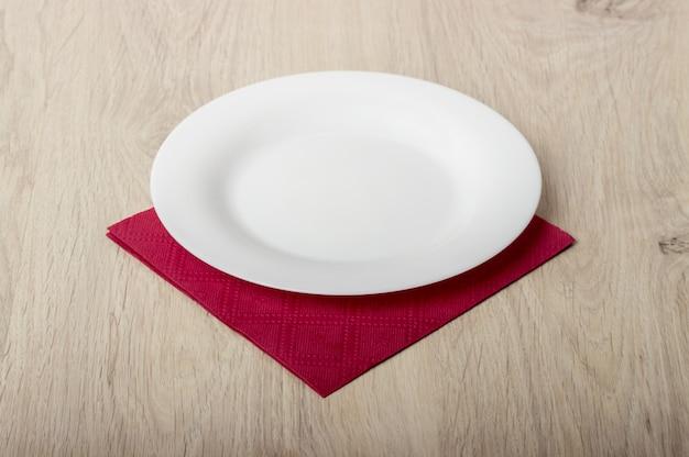 Assiette blanche vide sur une table en bois