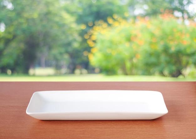 Assiette blanche vide sur la table sur la nature du parc flou en plein air au printemps et en été avec fond bokeh