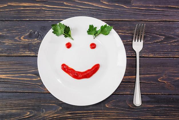Assiette blanche avec un visage souriant à base de ketchup et une fourchette sur une surface en bois.
