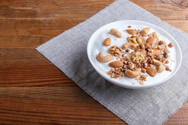 Assiette blanche avec yaourt grec, granola, amande, noix de cajou, noix de grenoble sur une surface en bois brune.