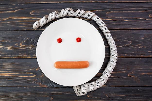 Assiette blanche avec yeux de saucisse et de ketchup, ruban à mesurer sur une surface en bois.