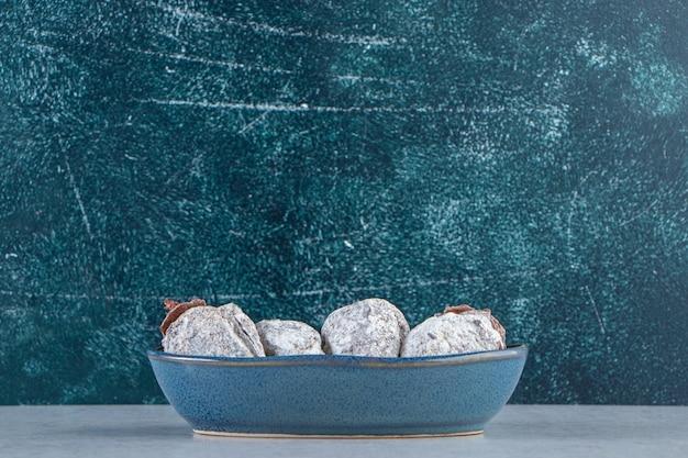 Assiette bleu profond de fruits de kaki séchés sur pierre.