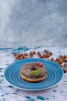 Assiette bleue avec beignet au chocolat et noisettes décortiquées sur une surface blanche.