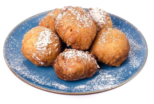 Assiette bleue avec des beignets ronds avec du sucre en poudre isolé.