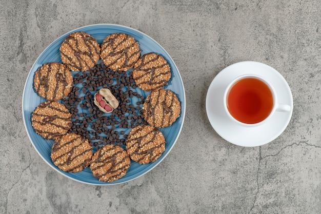 Assiette bleue avec biscuits au chocolat et tasse de tisane sur marbre.
