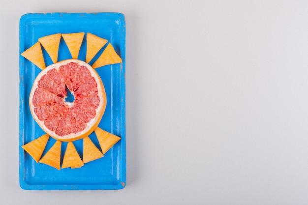 Assiette bleue de chips triangle et tranche de pamplemousse sur fond blanc. photo de haute qualité