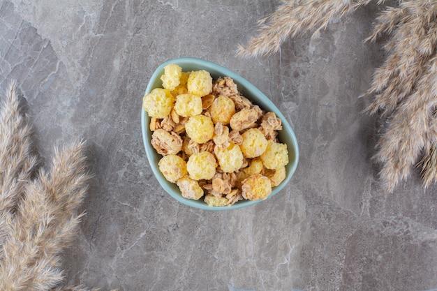 Une assiette bleue de cornflakes sucrés sains sur fond gris.