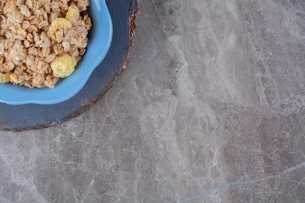 Une assiette bleue de cornflakes sucrés sains avec un pot de lait en verre sur une pièce en bois