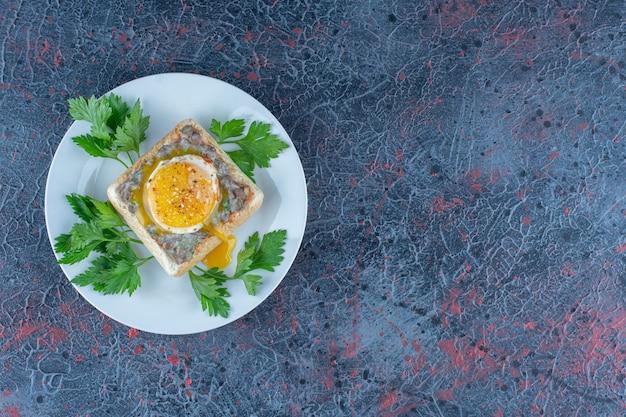 Une assiette bleue de délicieux toasts avec de la viande et des légumes.