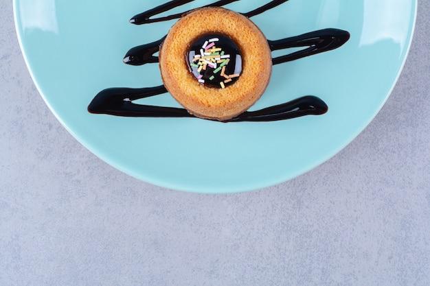 Une assiette bleue de deux beignets sucrés avec des pépites colorées.