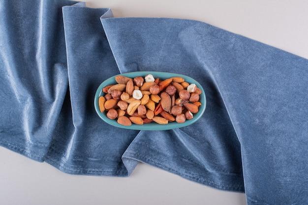 Assiette bleue de diverses noix biologiques sur fond blanc. photo de haute qualité