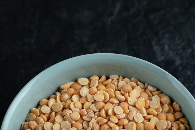 Une assiette bleue avec du maïs soufflé non cuit sur fond noir.