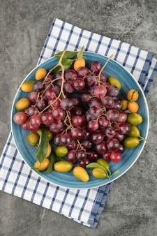 Assiette bleue de fruits kumquat et raisins rouges sur une surface en marbre.